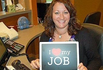 Team member with I love my job sign