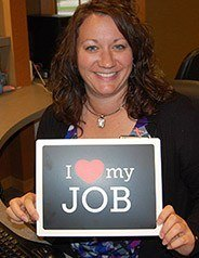 Team member smiling with I love my job sign