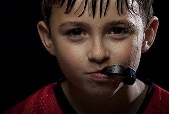 Young boy holding sportguard in mouth