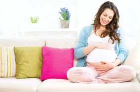 Smiling pregnant woman on the couch