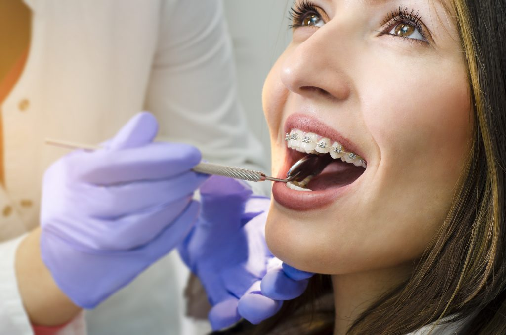 Woman with braces getting a checkup